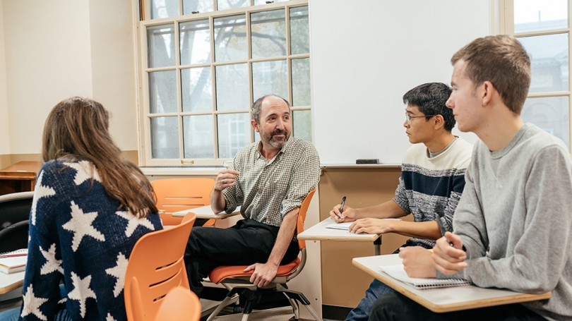 Professor Michael Herron talks with students in a classroom.