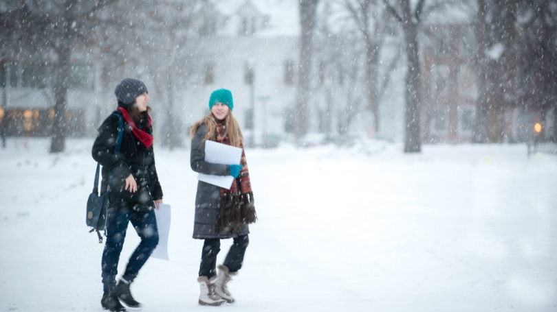 Two students walk through a snowstorm.