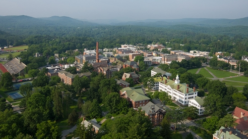 an aerial view of campus, with green trees and mountains in the background