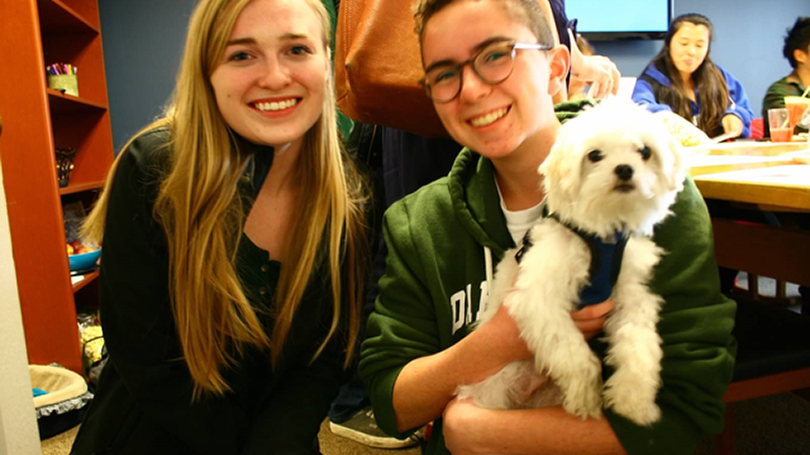 Two students cuddle a small therapy dog.