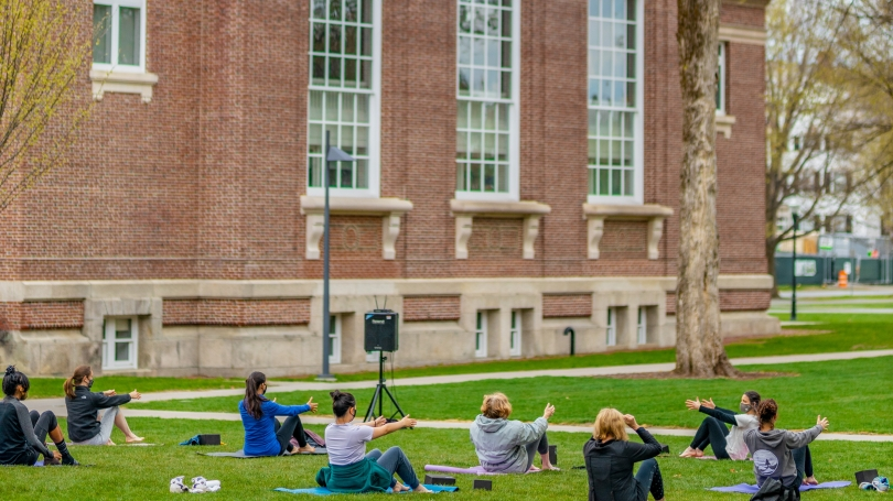 people on grassy area doing yoga boat pose in outdoor yoga class