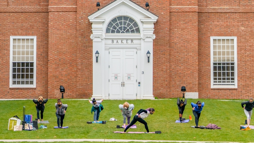 People practicing yoga on mats on green lawn in front of large brick building, Baker library