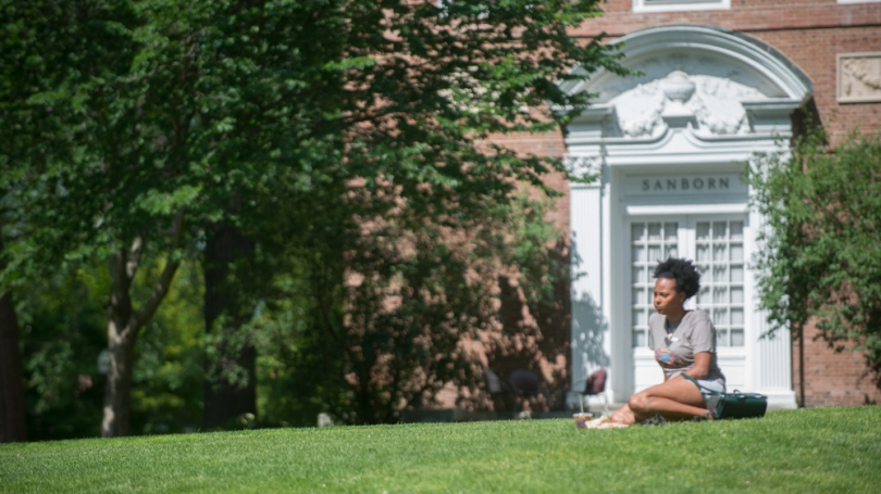 A student sitting quietly on campus in the sunshine.