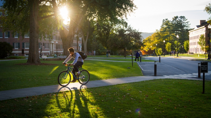 A student rides their bike across campus